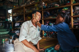 A local Palaung woman applies thanaka, the traditional makeup used for sun protection and beauty, to our trekking guide outside Hsipaw, Myanmar, May 2014.