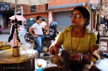 A local biker sips a masala tea (milk, sugar and spices) from a street vendor in central Kathmandu. Nepal, July 2014.