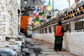 A woman spins the prayer wheels near a Buddhist temple in Kagbeni. Nepal, July 2014.