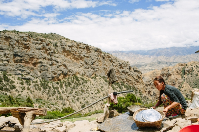 A lodge owner washes dishes in the village water source with the high desert of the Upper Mustang as a backdrop. We mostly ate in small family run lodges or hotel cafés where we were often the only patrons.