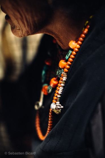 Colorful coral and stone beads make a stunning piece of jewelry on a local Tibetan woman. Nepal, July 2014.