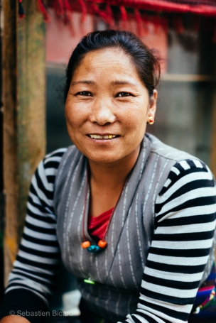 A shopkeeper smiles in front of her wares in Lo Manthang, Upper Mustang. Nepal, July 2014.