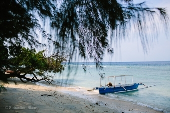 A small fishing boat off the white sands of tiny Gili Air, one of the three tiny islands off the coast of Lombok. There are no vehicles or law enforcement on any of these islands, and they can all be explored in a few hours, but appreciated for weeks. Indonesia, June 2014.