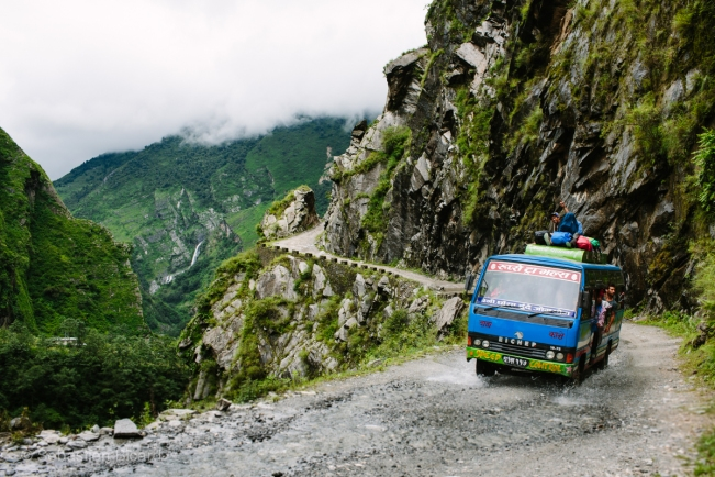 A nightmarish scene for me -  an old bus on a rocky cliff road. Note the locals riding on TOP of this bus.