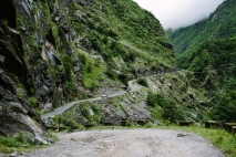 A scarily steep and rocky jeep trail leads winds through a lush green valley on the way to Jomsom. Nepal, July 2014.