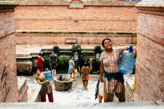 Local women fill up on clean water in a centuries-old bath house in Patan. Nepal, July 2014.