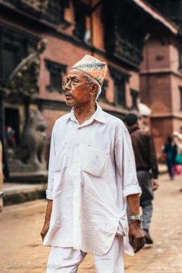 A man sports a dhaka topi, the traditional Nepali hat. Patan, Nepal, July 2014.