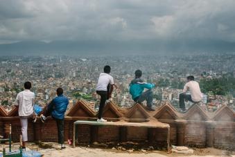Young men contemplate the sprawling capital city of Kathmandu from Swayambhunath stupa. Nepal, July 2014.